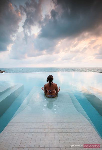 Asian woman doing yoga in an infinity pool at sunset, Thailand