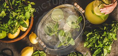 Fresh homemade citrus lemonade in tray over grey kitchen counter