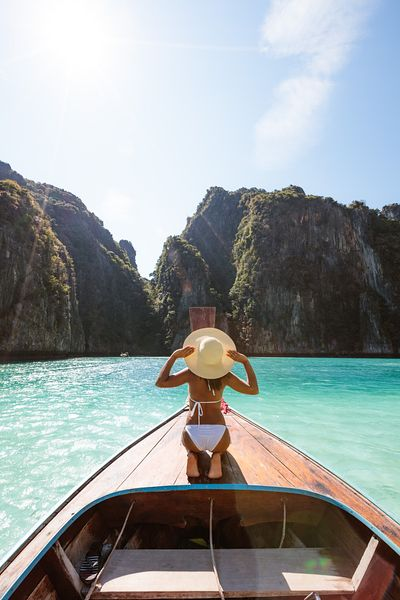 Woman holding straw hat on boat prow, Phi Phi islands, Thailand