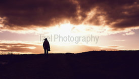 The silhouette of a hiker on the left of the frame against a fire red sky at sunset over the open moors.
