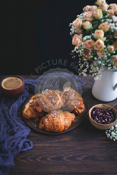 Croissants and a cup of coffee on a rustic wooden table