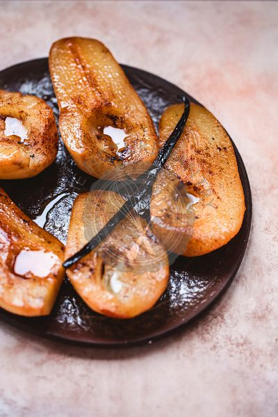 Roasted pears and vanilla pod on a ceramic plate