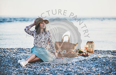 Young woman having picnic at sunset at seaside with appetizers