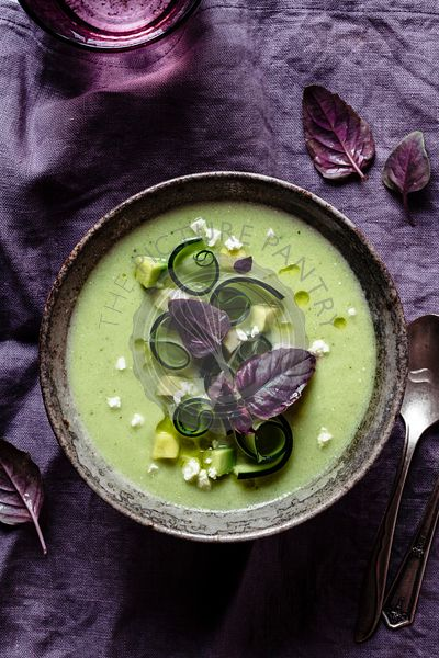 Green gazpacho on a purple napkin