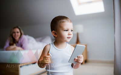 Toddler boy with his mother in bedroom at home using smartphone