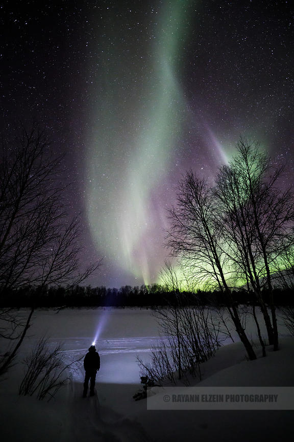 Man standing on the shore of the Kaamanen River under the northern lights
