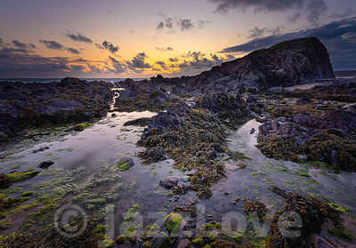 Dusk on scenic rocky beach in Freshwater West, South Wales, UK.