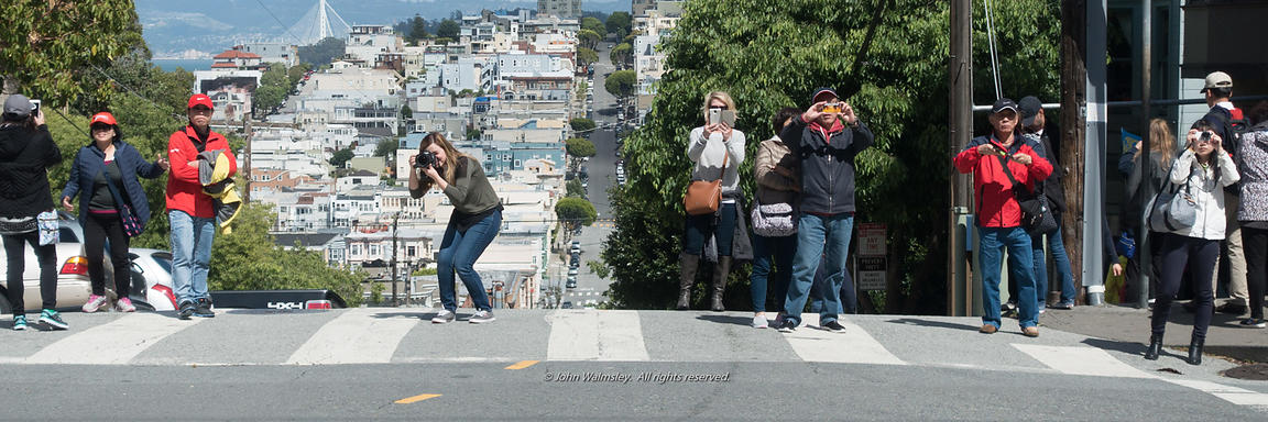 Tourists photographing the very crooked Lombard Street, San Francisco.