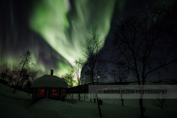 Northern lights above a fireplace hut on the shore of the Teno River in Lapland