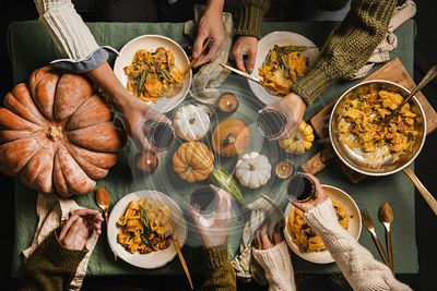 Friends celebrating Thanksgiving day with wine and squash pasta