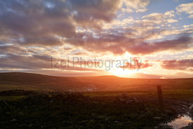 A stone wall and entrance to a farmers field near Bolts Law at Sunset.