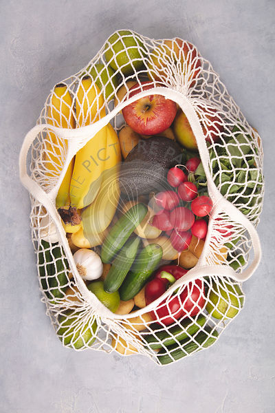Zero waste concept. Fresh organic fruits and vegetables in mesh textile bag, flat lay