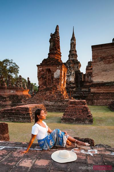 Asian woman at Wat Mahathat at sunset, Sukhothai, Thailand