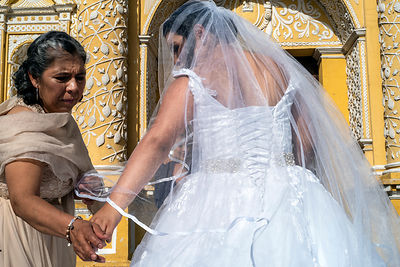 A mother adjusts her daughter's wedding dress