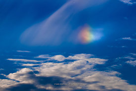 #73958,  Rainbow cloud above southern England.  The rainbow is seen when light reflects off tiny ice crystals inside the body...