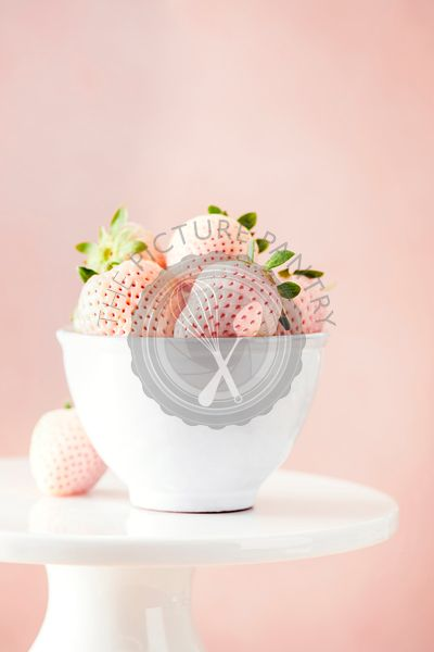 Bowl of fresh pineberries surrounded by soft, pink and white tones.