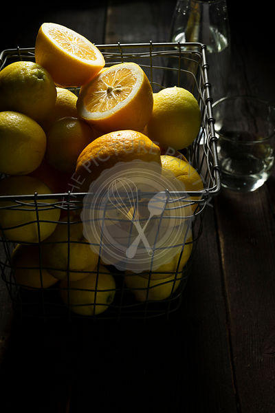 Home grown lemons in a square wire basket, on a rustic wooden background. A glass of water and carafe are in the background.