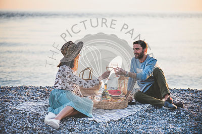 Young happy couple having picnic with sparkling wine at seaside
