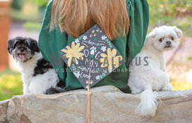 two small dogs posing behind dog mom wearing cap and gown