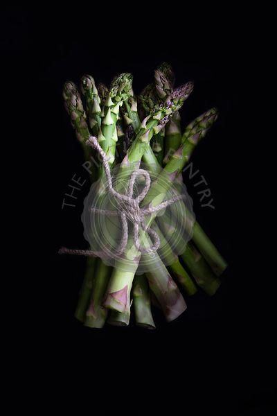 Brunch of fresh asparagus on a black background.