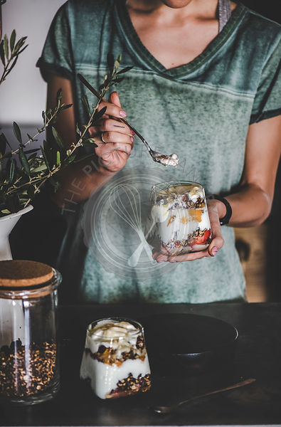 Woman having healthy vegan breakfast with yogurt in glass