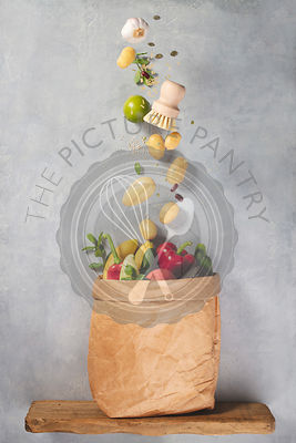 Grocery shopping concept. Fresh organic fruits and vegetables in paper bag. Levitation