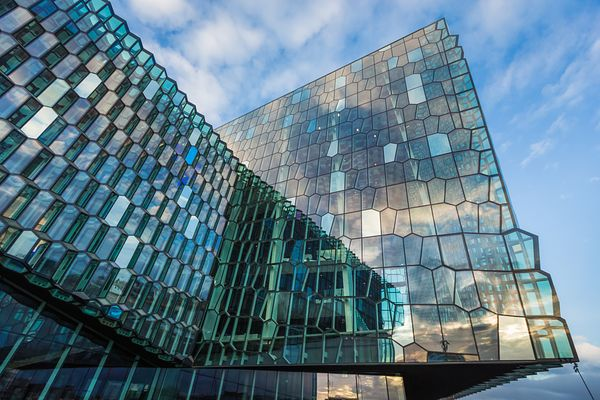 Partial view of Harpa's exterior facade reflecting daylight in its multi-faceted windows. The facade of this Reykjavik concer...