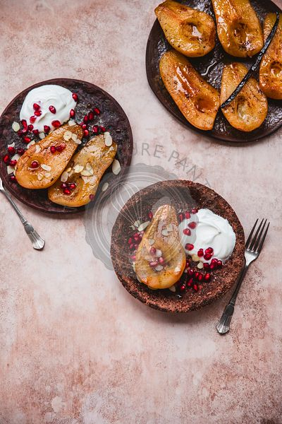 Roasted pears served with Greek yogurt, pomegranate seeds and almond flakes