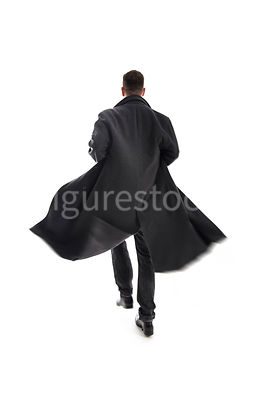 A Figurestock image of a mystery man in a long black coat, running away – shot from eye level.