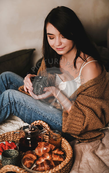 Young beautiful smiling brunette woman enjoying breakfast in bed