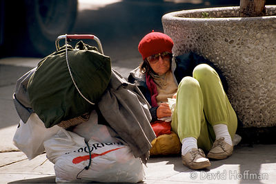 Homeless woman sitting on the street in San Francisco, California, USA.