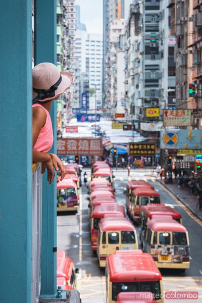 Woman looking at red buses in Mong Kok, Hong Kong