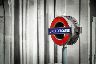 Red London Underground sign against columns in the City of London