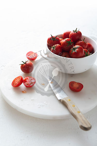 Freshly washed cherry tomatoes in a white colander, prepared for slicing.