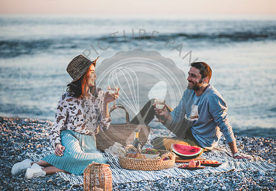 Young couple having picnic at seaside with wine