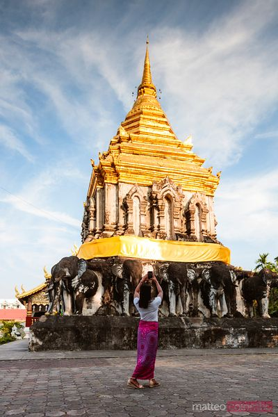 Woman taking a photo of Wat Chiang Man, Chiang Mai, Thailand