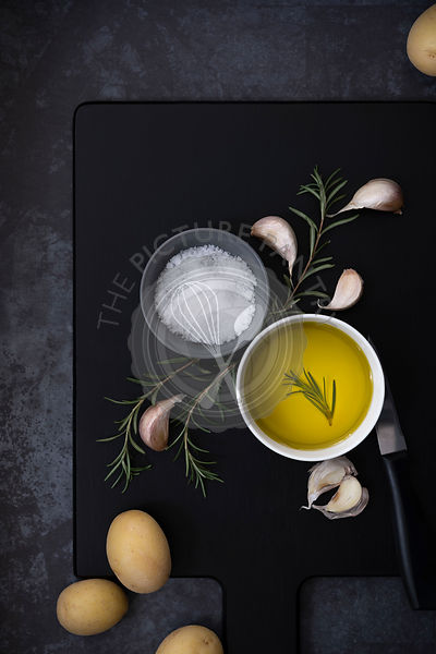A bowl of olive oil, salt flakes, rosemary and potatoes on a black wooden cutting board.