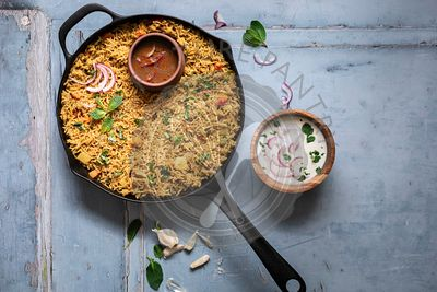 Vegetable Biryani in a cast Iron pan searved with Raita and Salan