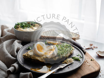 A backlit shot of a soft boiled egg, cut in half on a thin slice of bread covered with hummus and greens on a silver plate si...