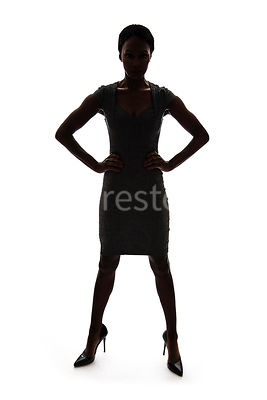 A tough woman, standing with hands on hips, in silhouette – shot from eye level.
