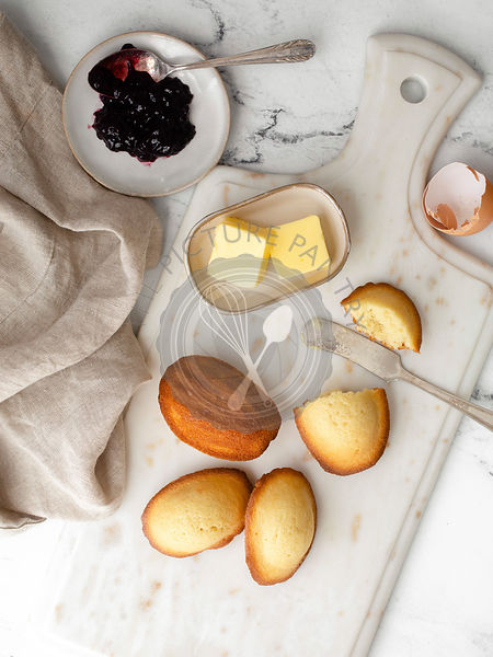 Slightly browned french madeleine cookies on a white marble countertop surrounded by silverware, jam on a saucer, an eggshell...