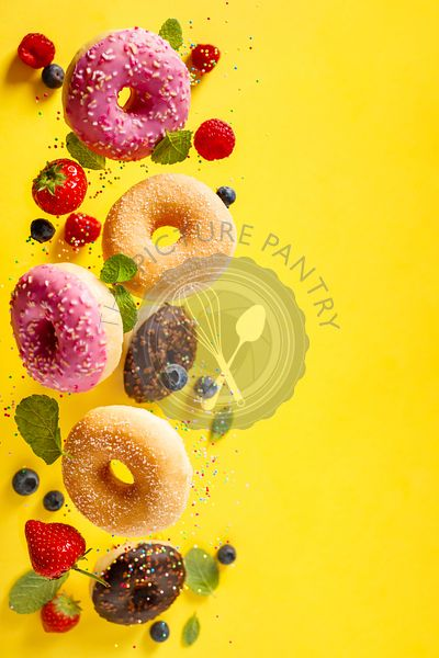 Various decorated doughnuts with sprinkles and berries in motion falling on yelloy background
