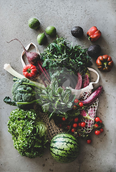 Fresh vegetables, greens and fruits over grey concrete kitchen counter