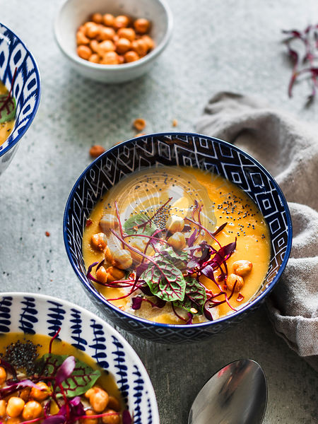 Creamy carrot parsnip soup with sorrel, chickpeas and microgreens