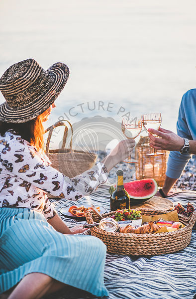 Couple having picnic at seaside with sparklng wine and fruit