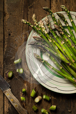 Fresh, raw asparagus on a vintage plate, on a timber background. A knife and cut asparagus ends are alongside.