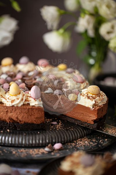 Serving slices of a no-bake chocolate cheesecake decorated with whipped cream, chocolate flakes and candy Easter eggs