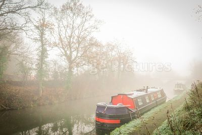 Red narrow boat on the Grand Union canal ib the mist