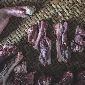 Hue Market, Vietnam, meat raw assortment on a dark wicker working table. Top view.