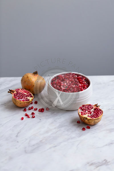 Pomegranate seeds in a white ceramic bowl on a marble table